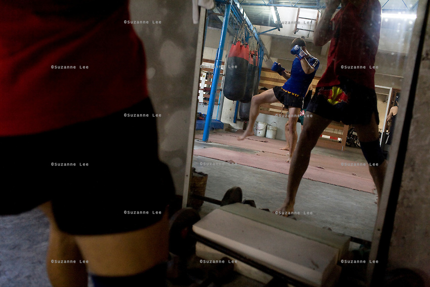 "Ilya (left in mirror) train with punching bags in Rompo Muay Thai Gym, Khlong Toei, Bangkok city, Thailand on 14th December 2009..Ilya Bashes, aged 27, from Herzeliya, Israel, has been fighting seriously for 5 years. He met Shuki in a muay thai seminar in Israel and decided immediately that he would come to Thailand to train under Shuki. ""I knew he was serious from the look in his eyes,"" says Shuki. Ilya has since been to Thailand 3 times, for 6 months each time. Ilya is rapidly gaining a good reputation in Thailand as a strong fighter. When back in Israel, he works as a Sushi chef in an expensive restaurant. Ilya 's family is of Russian heritage, very non-religious. ""Chabad keeps the people together yet it doesn't push religion on to people."".Photo by Suzanne Lee / For Chabad Lubavitch"