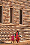 Mother and child walk by the diamond wall of the Palazzo dei Diamanti, originally a residential home of the Este family (built between 1493 and 1503) and acquired by the city in 1832, the palace is now the National Gallery of Art and Civic University