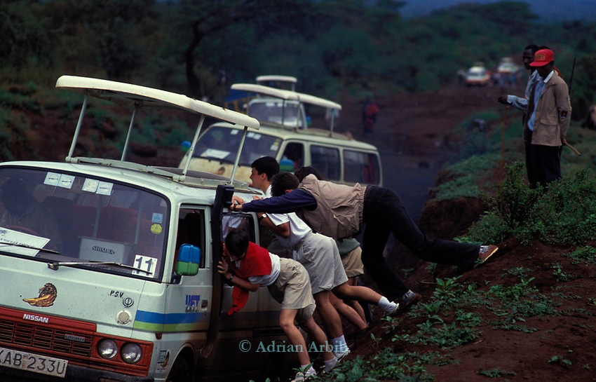 Tourists help to get their vehicle unstuck on a muddy road  in the Maasai mara game park.  <br /> The name of the park means Maasai blood following the wars that were fought to keep their land from the British colonizers.<br /> Now it is illegal for Maasai to enter the park to graze their animals.   <br /> Instead thousands of tourists visit the park every month<br /> bringing in valuable foreign exchange for the Kenyan government.