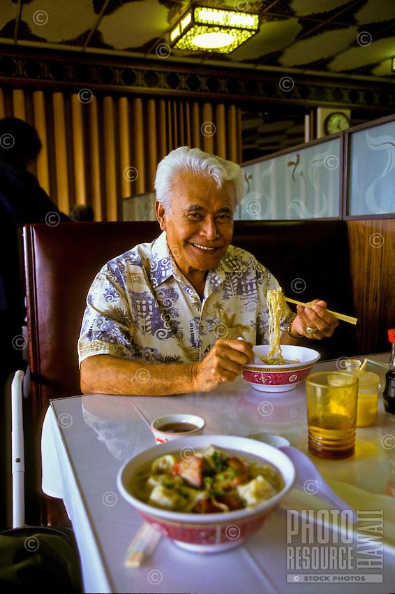Hawaiian man in restaurant eating wo gau gee mein (dumplings, pork, shrimp, vegetables, noodles); Kaneohe, Windward Oahu