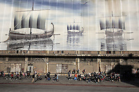 Pictured: Migrants against a mural, as they arrive to the port of Piraeus Monday 22 February 2016<br /> Re: Thousands of migrants, most from Syria, have landed to the port of Pireaus, after crossing the border from Turkey to various islands like Lesvos and Kos in Greece.