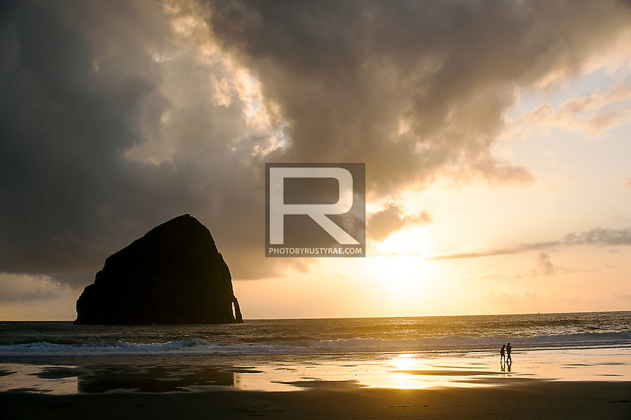 A couple enjoys sunset on the beach at Haystack Rock in Pacific City, OR.