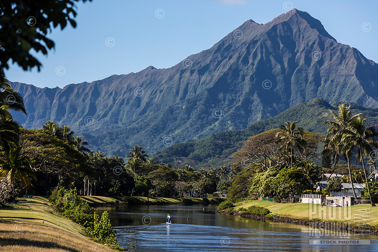 A standup paddler in a Kailua canal, with the Ko'olau range in the distance, Windward O'ahu.
