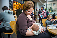 A mother looks at her baby as she breastfeeds in a museum cafe.<br /> <br /> London, England, UK<br /> 08/03/2015<br /> <br /> &copy; Paul Carter / wdiip.co.uk