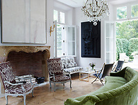 The family room opens on to the garden terrace and has a light and airy atmosphere.  A curving green sofa faces the antique fireplace surround; the 19th-century gilt bronze-and-crystal chandelier is French.