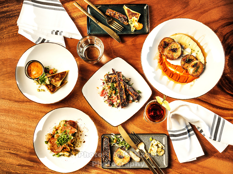 Dishes and interior dinning area at El Five restaurant in Denver, Colorado, Wednesday, October 18, 2017. Dishes include patatas bravas, lamb ribs, crispy cauliflower Yufka, shrimp &amp; calamari a la plancha and a Spanish scaffa cocktail.<br /> <br /> Photo by Matt Nager
