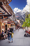 Street scenery of people, shops and restaurants on Banff Avenue, downtown of Banff in Alberta Rockies with Rocky Mountains in the background. Alberta, Canada 2017