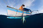 Outrigger boats catch yellowfin tuna fishing with hook and line. Catching a yellowfin tuna, these fishermen fish near a fish attracting device or rumpon, attached to a raft or rakit some 100 km from Gorontalo. Some men had been living on their boat & FAD for almost two months.