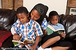 mother at home with sons, reading to 6 year old boy with 8 year old son reading to himself in background horizontal
