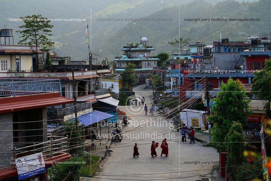 NEPAL Pokhara, tibetan refugee camp Prithvi, new buildings of Nepali people, tibetan monk with novices / NEPAL Pokhara, tibetisches Fluechtlingslager Tashi Ling, Blick auf angrenzende Haeuser von Nepali, auf der Strasse alter tibetischer Moench mit Novizen