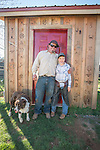 Clinton Brownlie with nephew Michael Blake and cow dog.<br /> <br /> The Busi family and friends use hot irons to christen and brand the new pump shed at their corrals near Jackson, California.