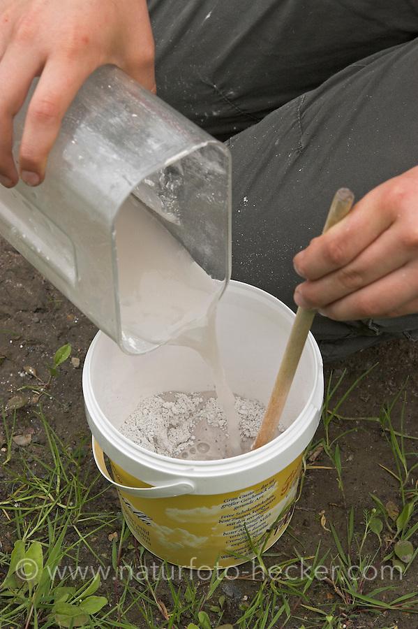 Kinder gießen Tierspur aus Gips, Mädchen rührt Gips in altem Becher an