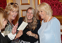12 July 2016 - London, England - Camilla, Duchess of Cornwall, laughs with her daughter Laura Lopes and Annabel Elliot as she hosts the 30th Anniversary Garden Party for the National Osteoporosis Society in St James Palace in London. Due to inclement weather the event was moved indoors. The Duchess of Cornwall has been connected with the charity for nearly 30 years. Photo Credit: ALPR/AdMedia