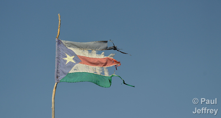 The flag of South Sudan, a little worse for wear, flies over the market in the town of Alek.