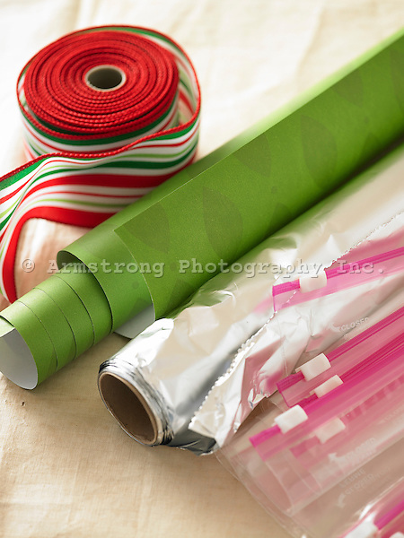 Green and silver rolls of gift wrap and a roll of ribbon