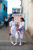 PHILIPPINES, Palawan, Puerto Princesa, young female nurses in Central Puerto Princesa wait for their ride near the Mitra Amphitheater