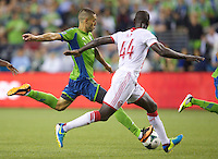 Clint Dempsey, left, of the Seattle Sounders FC takes a shot against Pa Modou Kah during play at CenturyLink Field in Seattle Saturday August, 3, 2013. The Sounder won the match 1-0.