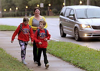 NWA Democrat-Gazette/DAVID GOTTSCHALK Rhonda Bramell, walks Wednesday, October 10, 2018, with twins Carley (left) and Evan, both third grade students at Walker Elementary School, to school in Springdale. Walker Elementary School participated in National Walk to School Day. Studies have shown that walking to school positively influences academic achievement, student morning energy levels, attention, truancy, and absenteeism.