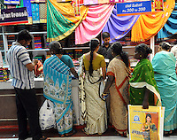 Ladies choose Sari / Saree material from very colourful collection at the Sari / Saree dress shop in Madras, India
