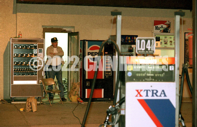Laurel Springs Police Chief George Kralley guards the doorway of the murder scene at the Xtra gas station on the White Horse Pike in Laurel Springs, NJ., waiting for detectives to return to the murder scene for further investigation, early Thursday morning(ABOUT 1:30AM) In the foreground is an Xtra gas pump.