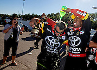 Sep 29, 2013; Madison, IL, USA; NHRA top fuel dragster driver Antron Brown (right) douses a crew member with Mello Yello as they celebrate after winning the Midwest Nationals at Gateway Motorsports Park. Mandatory Credit: Mark J. Rebilas-