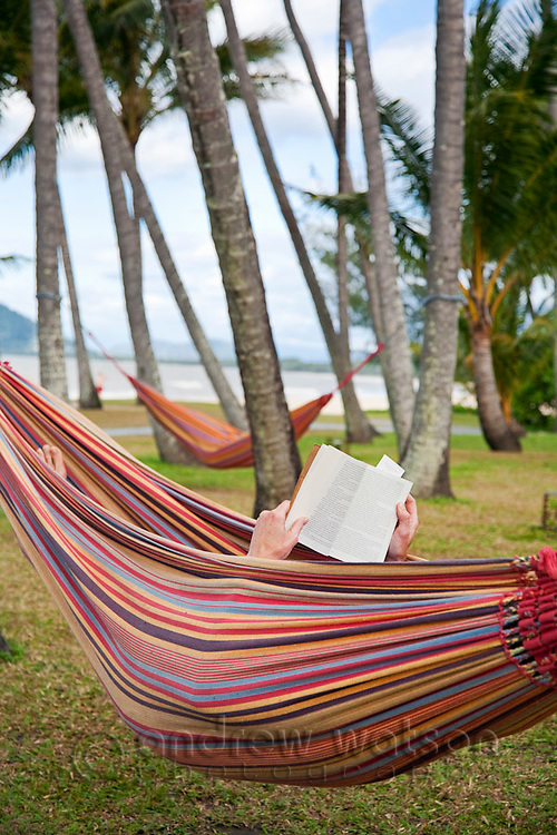 Man relaxing in hammock reading a book.  Palm Cove, Cairns, Queensland, Australia
