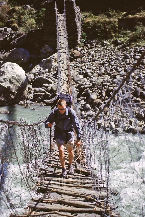 A man hiking across a bridge on the trek towards Mount Manaslu in Nepal.