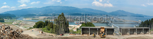 Photo shows the view from a hilltop overlooking Rikuzentakata, Iwate Prefecture, Japan. Atlas Copco drill rigs are a key feature of the project, which will shift blasted rubble from a nearby hillside to the central part of the city, which was flattened by the 2011 tsunami, where the land will be raised 10 meters. Rubble is transferred to the lower lying coastal land via a 3-km-long conveyor belt system, which spans the river and zig-zags its way across the city. Rob Gilhooly Photo