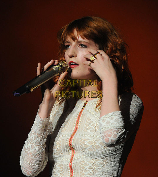 FLORENCE WELCH of Florence And The Machine.performs to a sold out crowd at The Wiltern in Los Angeles, California, USA, November 6th 2010..music concert gig on stage half length white rings hand microphone   dress zip singing hand  patterned long sleeve                                                                                                                            .CAP/RKE/DVS.©DVS/RockinExposures/Capital Pictures.