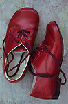 Pair of young childs lace-up red shoes shiny but slightly scuffed lying with one on its side on marbled slate