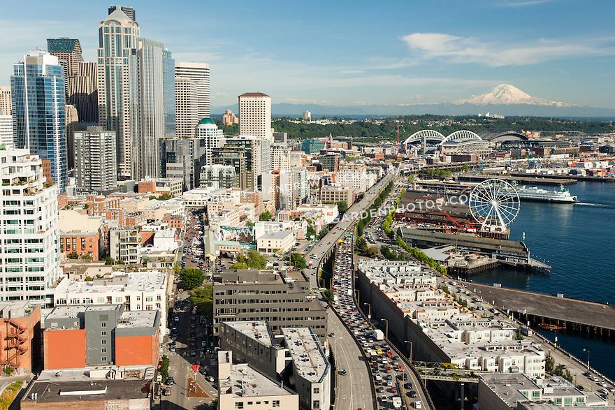 Seattle downtown skyline, waterfront, Alaskan Way viaduct, and the Seattle Great Wheel ferris wheel with Mount Rainier behind; Seattle, WA