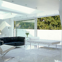 White Barcelona chairs and a daybed compete with a black Le Corbusier sofa in the living area of the penthouse