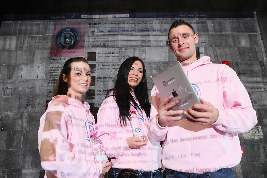 NO Repro Fee.27/10/2010.  Ballygowan Pink's B Part Of It campaign in support of Breast Cancer Awareness Month. Hundreds of UCD students got behind Ballygowan Pink's B Part Of It campaign in support of Breast Cancer Awareness Month. Pictured are  Paulina Mastalska, Paul Murry and Ciara Parmer from Dublin who posted messages of support to the life-sized Facebook Wall which was projected onto the entrance of UCD library. A live stream of students' messages was seen throughout the day to raise awareness of breast cancer and support the Marie Keating Foundation. Picture James Horan/Collins Photos