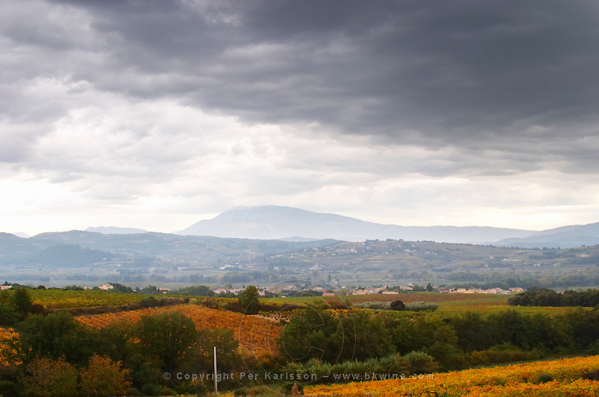 The Mont Ventoux from the north from a distance the top covered in snow. in mist, valley with villages in front, vineyards, storm clouds. Vaucluse, France, Europe