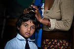 A young girl has her hair combed as she gets ready to go to school at an orphanage in Pokhara, Nepal.