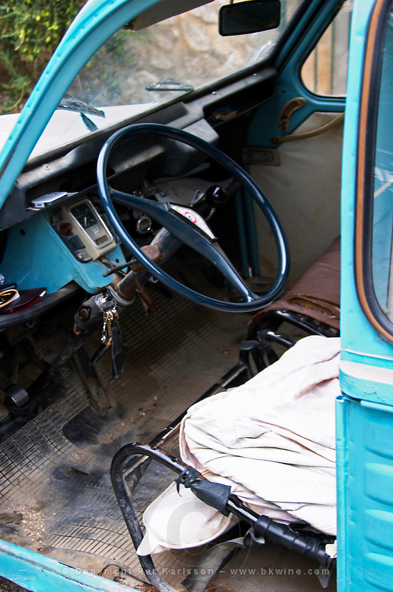 A blue old Citroen 2CV 2 CV converted into a transport van. Inside the driver seat and steering wheel, falling apart. Moulin Mas des Barres olive mill, Maussanes les Alpilles, Bouches du Rhone, Provence, France, Europe