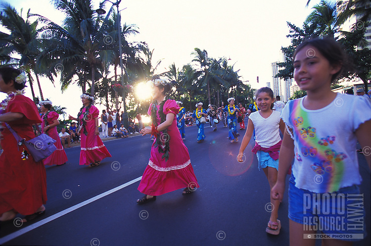 Girls watch Japanese women in hula muu muu's at the Pacific Asian Parade in Waikiki, Hawaii