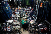A boy sleeps among packages of blue jeans in a wholesale market at Fuzi Miao in Nanjing, Jiangsu, China.