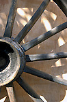 Cart wheel against old wall.