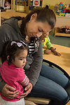 Education Preschool child care toddler 2s program female teacher with girl at start of day right after mother's departure separation