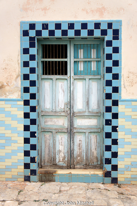 Old wooden door surrounded by colourful tiles in Santa Elena, Yucatan, Mexico..