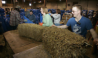 Thursday, Feb. 9, 2006  Anchorage, Alaska.  Several of the thousands of Iditarod volunteers work to bag and stack some of the 2,000 bales of straw which will be flown out to 20 checkpoints along the trail.  When a musher arrives at checkpoint, each  is given one bale of straw to bed their dogs down.