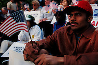 (970522-SWR08)--File Photo -- New York, NY -- A man holding  an american flag. Thousands of immigrants who gathered in Battery Park, in the shadow of the Statue of Liberty and Ellis Island, for a Rally for Immigrants Rights.  Photo © Stacy Walsh Rosenstock