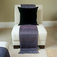 A pleasing contrast in colour and texture is created in the living room with the juxtaposition of a dark purple velvet cushion and violet linen runner against an oatmeal linen armchair