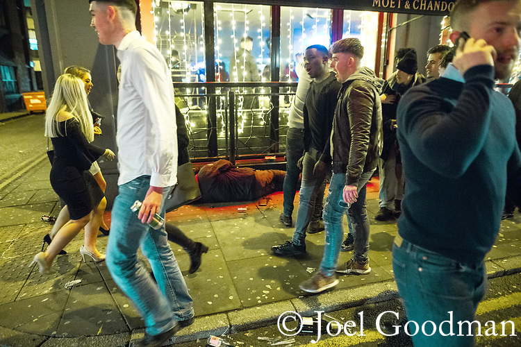 "© Joel Goodman - 07973 332324 . 15/12/2017. Manchester, UK. A man , believed to be homeless , sleeps on the pavement in front of a club on Peter Street , as revellers walk around him . Revellers out in Manchester City Centre overnight during "" Mad Friday "" , named for historically being one of the busiest nights of the year for the emergency services in the UK . Photo credit : Joel Goodman"