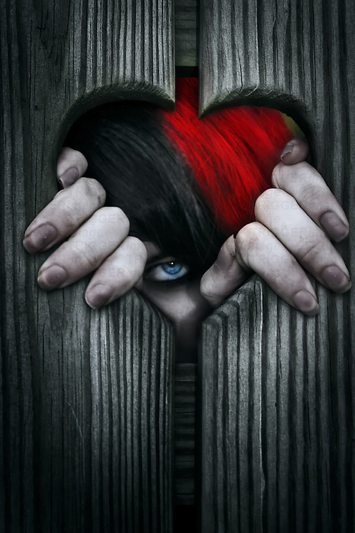 Young female with dirty fingers looking out of a wooden heart