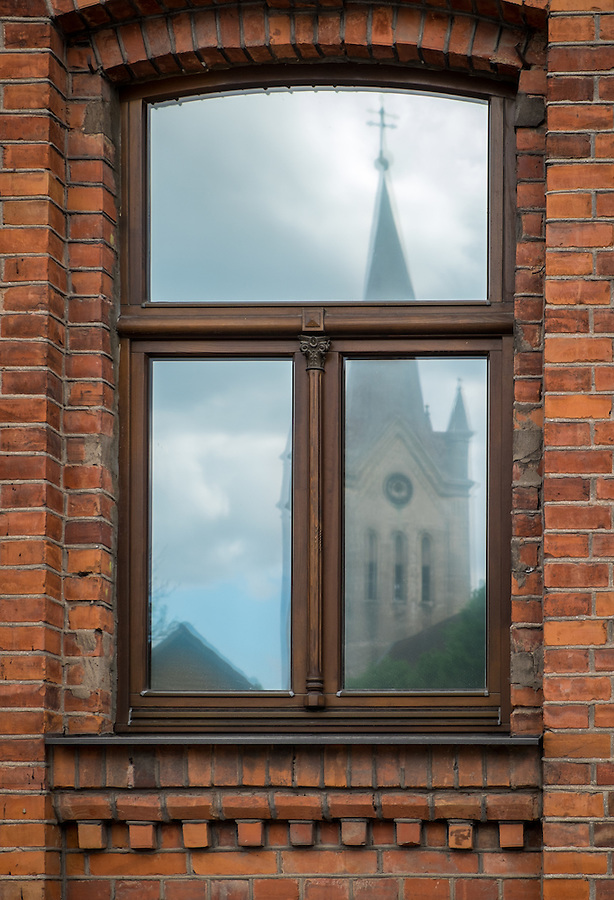 LATVIA, CESIS - CIRCA JUNE 2014: View of tower of the St. John's Church reflected in a window of an old buildinig in Cesis in Latvia.