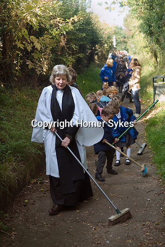 Old Mans Day Braughing Hertfordshire October 2nd. 2015. The vicar the Rev'd Julie Gawthrope sweeping Fleece Lane from the Fleece Inn leading to St Marys the Virgin church with the help of children from Jenyns First School.<br />