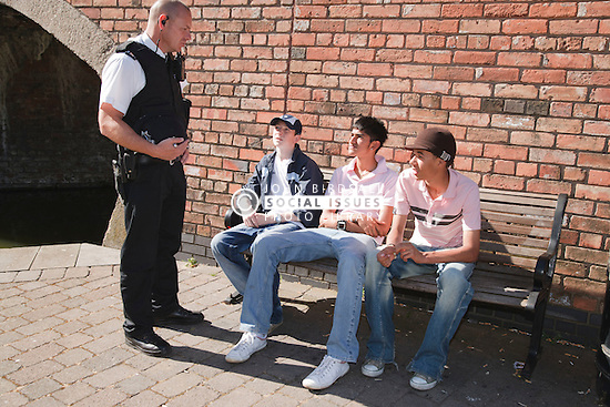 Policeman talking to group of teenage boys.