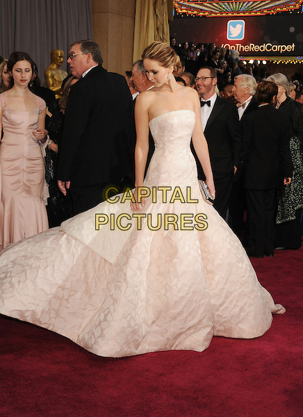 Jennifer Lawrence (wearing Dior Haute Couture).85th Annual Academy Awards held at the Dolby Theatre at Hollywood & Highland Center, Hollywood, California, USA..February 24th, 2013.oscars full length white pale pink strapless dress gown voluminous clutch bag full-tiered skirt profile looking down .CAP/ROT/TM.©Tony Michaels/Roth Stock/Capital Pictures